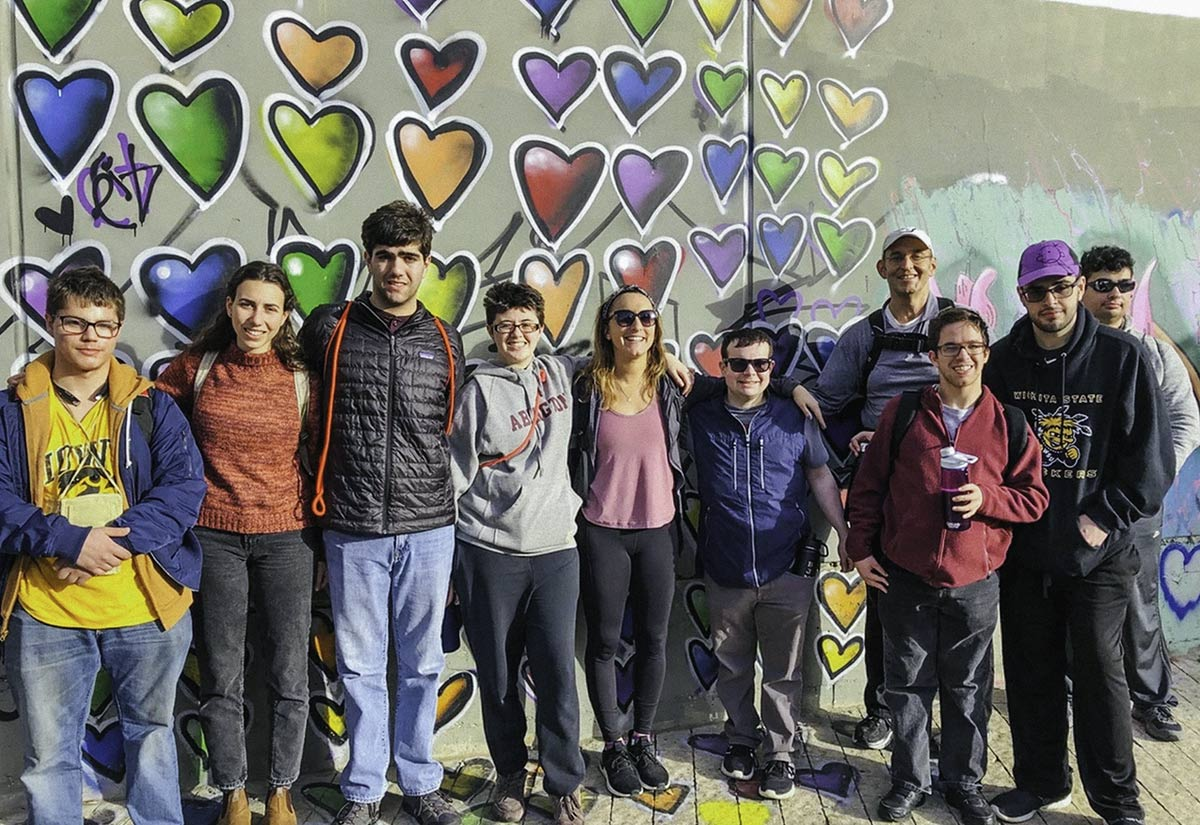 Jonah Geer with his Birthright Israel group in front of graffiti hearts in Tel Aviv