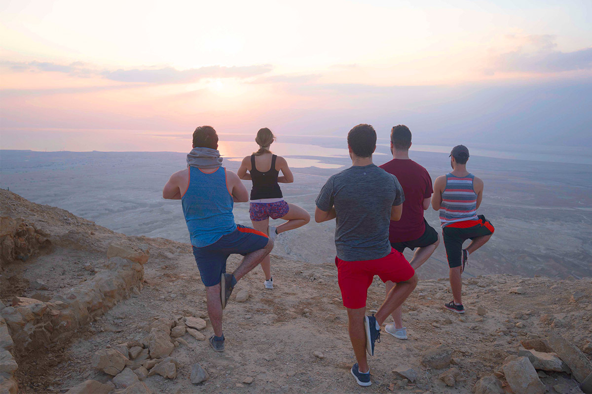 Birthright Israel participants doing yoga on a mountain.